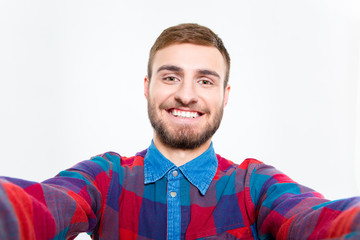 Selfie photo of happy smiling bearded guy in plaid shirt