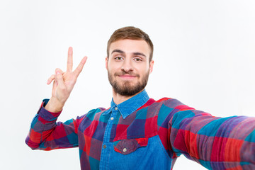 Selfie photo of positive handsome young man showing victory sign