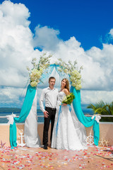 Happy bride and groom having fun on a tropical beach under the p