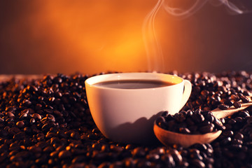 Cup of coffee and coffee beans on dark background