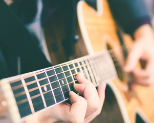 Young man playing guitar. Music, instrument education and learning concept