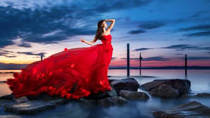 Schöne Frau im roten Kleid bei Sonnenuntergang am See