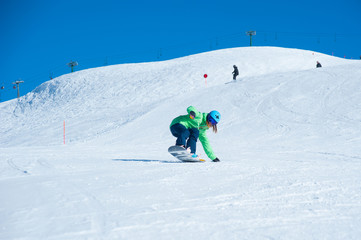 Female snowboarder running down in the mountains. Italian alps, Livigno. Resort Mottolino.