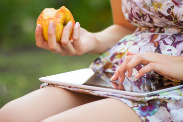 young woman eat apple and play on tablet pc in park