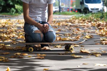 Ноги в рваных джинсах сидя на скейтборде. Парк, осень.  Дорога. Опавшие, желтые листья
