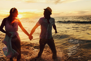 beautiful sunset in the ocean and happy couple holding hands