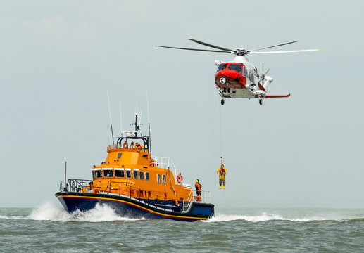 Orange sea rescue boat with rescue helicopter