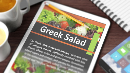"Tabletop with various objects focused on tablet with recipe of ""Greek Salad"" on screen"