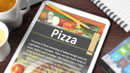 "Tabletop with various objects focused on tablet with recipe of ""Pizza"" on screen"