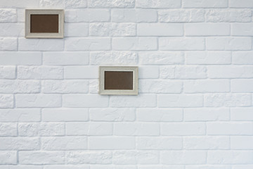 Empty picture frame at white brick wall