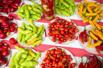 Colorful hot peppers in bright red, yellow, and green piles at farmers market display in Rio de Janeiro, Brazil