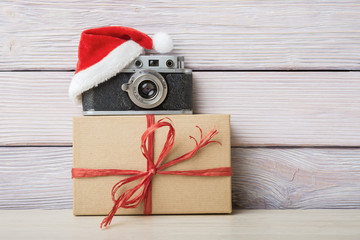 Vintage camera in santa hat and gift box over wooden background
