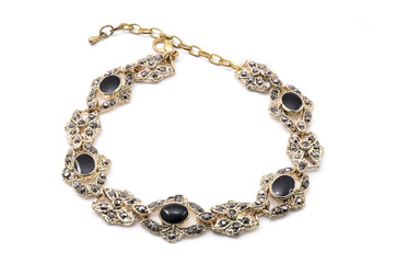 gold bracelet with black stone on a white background