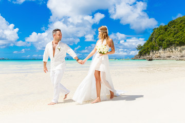 Happy Bride and Groom having fun on the tropical beach. Wedding