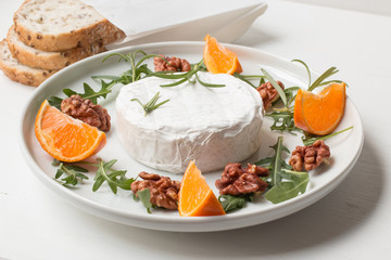 Camembert.Camembert cheese on the plate with fruits and nuts.