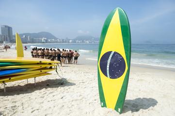 Brazilian flag surfboard stands in front of a lifeguard training course on Copacabana Beach in Rio de Janeiro, Brazil