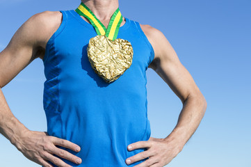 Athlete standing with gold medal in the shape of a heart hanging from Brazil colors yellow and green ribbon against blue sky