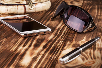 mobile phone, pan and sunglasses on the wooden background