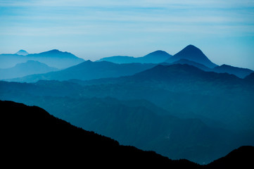 Black Mountain Silhouette in front of Skyscape cold blue mountains with mist and fog close to Quetzaltenango
