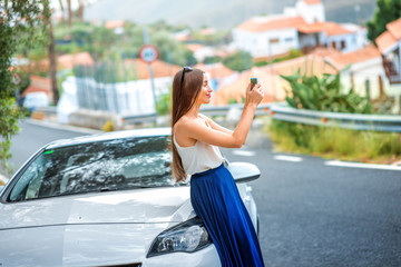 Young female traveler photographing with phone near the car