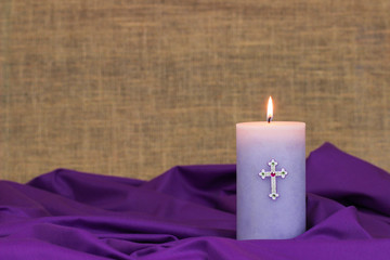 Purple Easter candle burning with fabric and burlap background