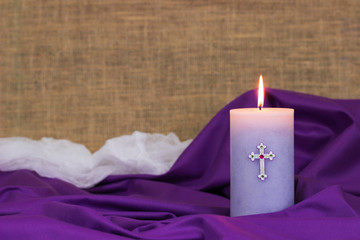 Purple Easter candle by fabric, white cloth and burlap blurred in background