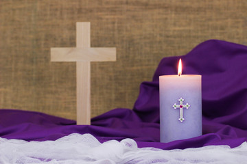 Purple Easter candle burning with fabric and blurred wooden cross in background