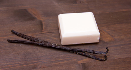 Soap vanilla with vanilla pods on wooden table