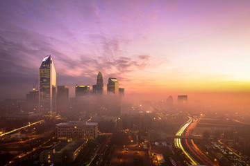 A foggy and colorful sunrise in Charlotte, North Carolina during the morning rush hour traffic.
