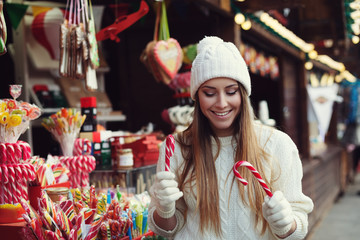 Street portrait of smiling beautiful young woman choosing candy canes on the festive Christmas fair. Lady wearing classic stylish winter knitted clothes. Close up