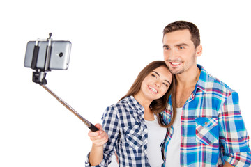 Cheerful cute couple in love making selfie photo with selfie sti