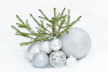 Little spruce tree on snowy ground with Christmas bauble ornaments at bottom