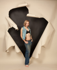 Girl in lingerie and jeans in ragged hole in the paper.