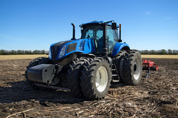 Fototapete - Blue tractor with plow