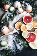 Citrus juice and slices of orange, grapefruit, lemon in new year tree decorations frame with snow on background