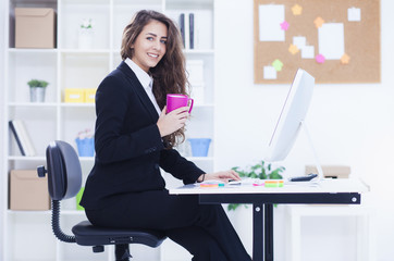 Beautiful business woman working on computer. Woman in her office, shallow depth of field