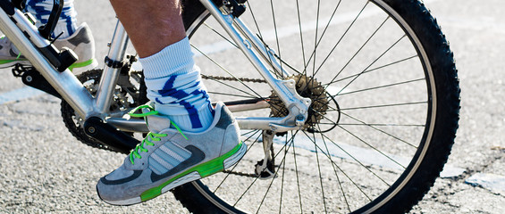 Sportsman feet while riding bicycle in the city