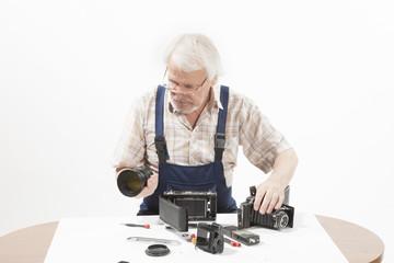 Man repairing an old camera