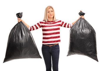 Displeased woman holding two trash bags