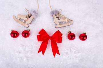 Xmas or new year composition with holiday decorations - little cristmas baubles on snow, red satin bow and toy skates on snow background. Christmas card
