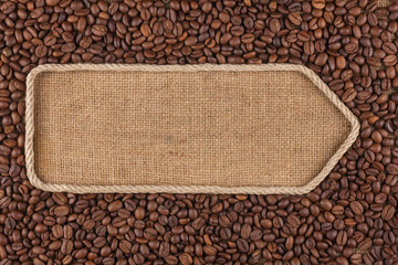 Pointer made from rope with coffee beans lying on sackcloth