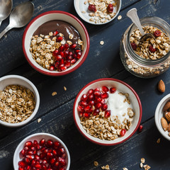 Healthy Breakfast - yogurt with homemade granola and pomegranate on a dark wooden board. Top view