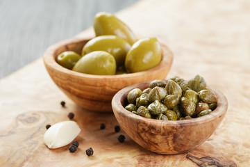 green huge olives and capers on wood table