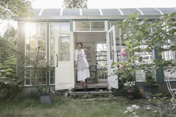 Senior woman standing in a greenhouse, Bavaria, Germany