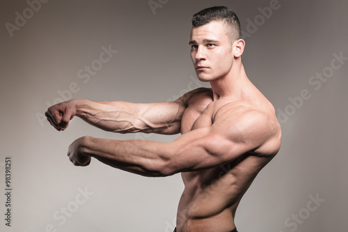 muscular fitness man shows arm muscles\