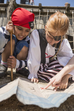 Two girls examining a treasure map in a adventure playground, Bavaria, Germany