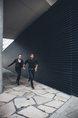 Black dressed young couple running hand in hand in front of black facade