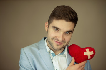 Happy man holding heart with medical tape