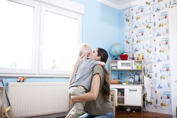 Mother and little son together at children's room
