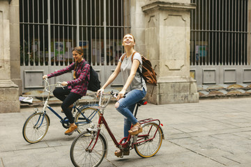 Spain, Barcelona, two young women riding bicycle in the city